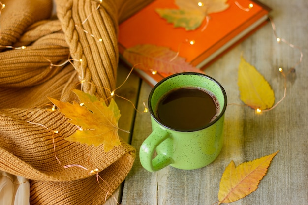 Mug of hot chocolate on a wooden table, still life with a book and yellow leaves and garlands