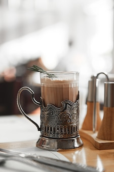 A mug of hot cocoa with a rosemary branch in a vintage metal cup holder.
