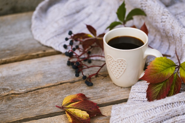 Mug of hot coffee in autumn setting on a wooden table with a knitted scarf, sweater