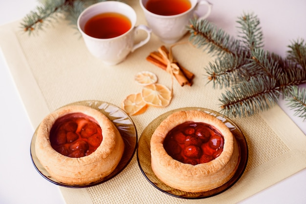 A mug of hot tea and cake. christmas card. the branch of the tree is spruce.