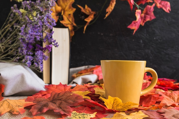Mug on leaves near books and flowers