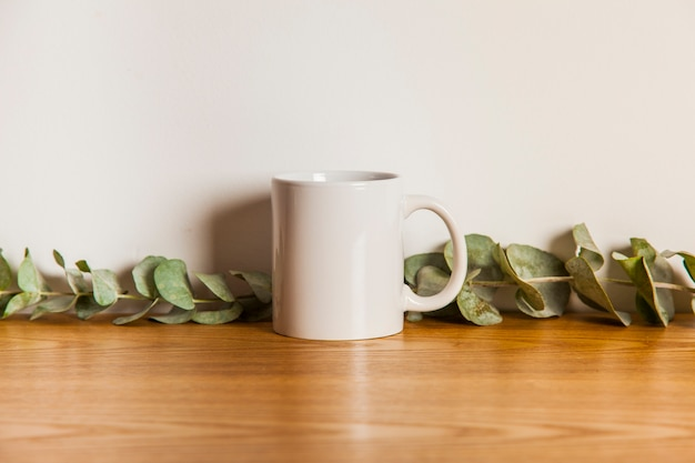 Mug and leaves on wooden surface