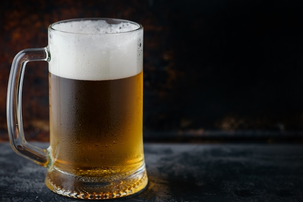 Mug of light beer with drops of water on a dark rusty background copy space