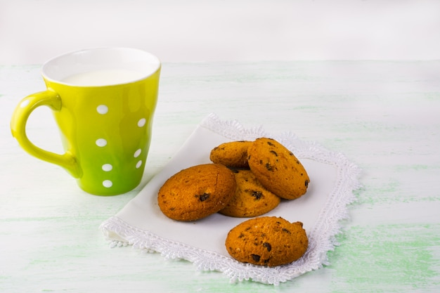 Mug of milk and cookies on white plate