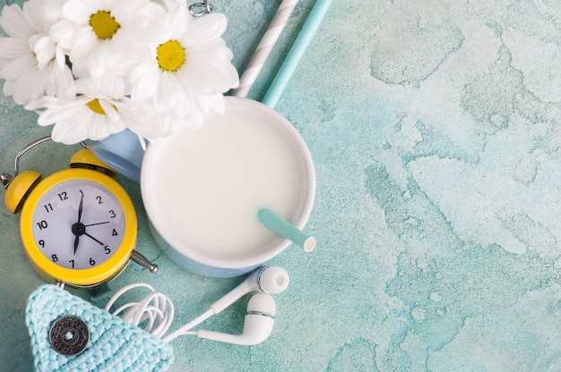 A mug of milk with straw, headphones and clock