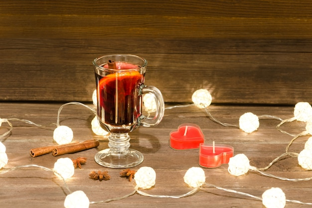 Mug of mulled wine with spices, candles and lanterns on a wooden table