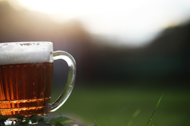 草の上のビールのマグカップ