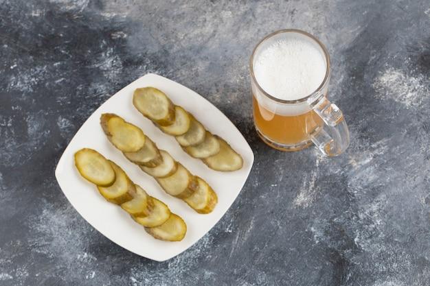 Кружка пива с тарелкой маринованных огурцов на каменной поверхности