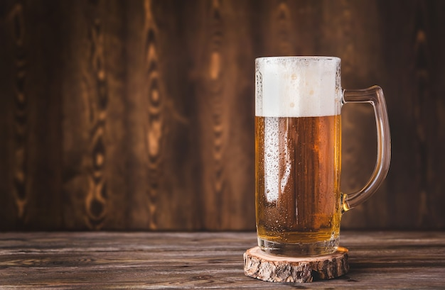 Кружка пива с пеной на деревянном столе