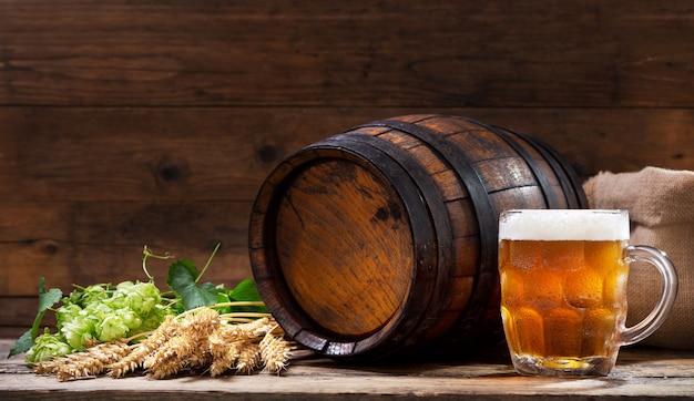 Кружка пива с зеленым хмелем и колосьями пшеницы на деревянном столе