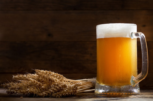 Кружка пива с колосьями пшеницы на деревянном столе