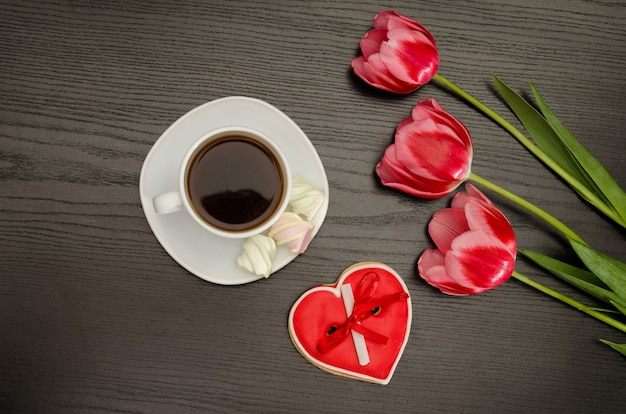 Кружка кофе, зефир и пряники в форме сердца, три розовых тюльпана. черный фон.