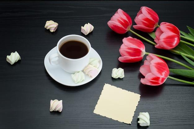Кружка кофе, зефир, пустая открытка и розовые тюльпаны. черный фон.