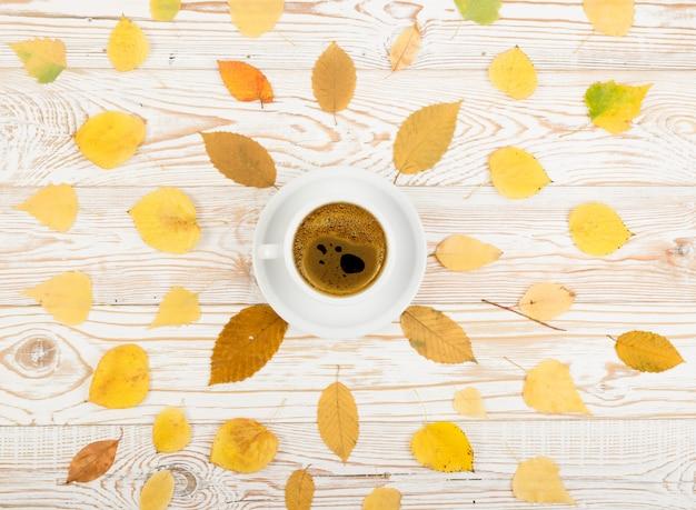 秋の木の葉に囲まれたコーヒーのマグカップ