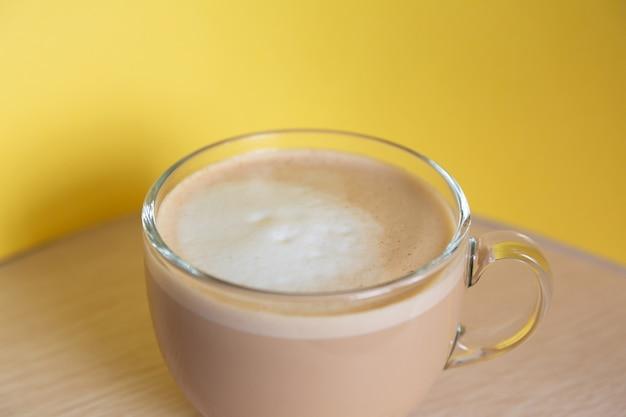 黄色の背景にミルクと泡とコーヒーのマグカップ朝のエネルギーと陽気さ