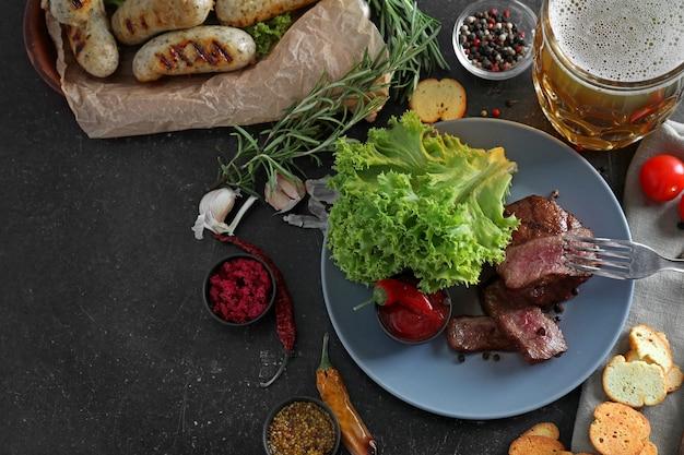 회색 테이블에 구운 스테이크, 소시지, 향신료와 함께 맛있는 맥주 머그잔