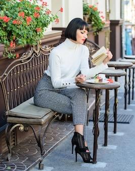 완벽한 주말을 위한 좋은 커피와 기분 좋은 책의 베스트 조합. 여자는 좋은 책 카페 테라스를 즐길 수 있습니다. 자기 개선 개념입니다. 여성을 위한 문학. 소녀 음료 커피 책을 읽습니다.