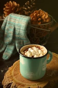 Кружка горячего какао с зефиром и перчатками на черном столе