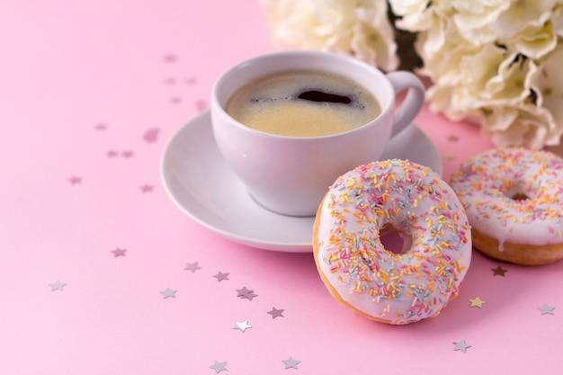 ホットカプチーノとピンクの花を持つ2つのドーナツのマグカップ