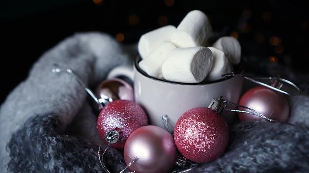 어두운 배경에 마시멜로가 든 핫 초콜릿 머그, 핑크 크리스마스 공이 있는 겨울 크리스마스 뜨거운 음료 - 근접 촬영 사진