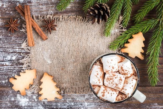 Кружка горячего шоколада с зефиром, специями, рождественским имбирным печеньем, еловыми ветками и шишками на темном деревянном фоне. скопируйте место для текста. рождественские обои, открытка.