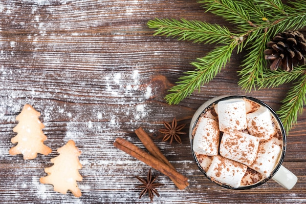 ダークウッドの背景にマシュマロ、スパイス、クリスマスジンジャークッキー、モミの枝とコーンとホットチョコレートのマグカップ。テキスト用のスペースをコピーします。クリスマスの壁紙、カード。