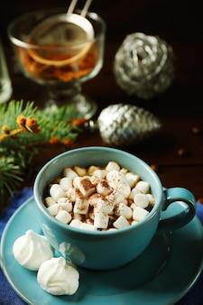 マシュマロ、木製の背景にモミの木の枝とホットチョコレートのマグカップ