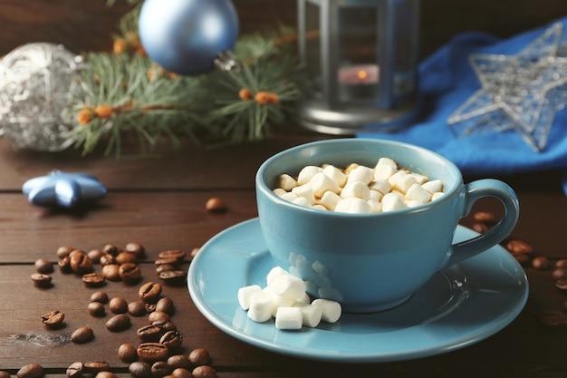 Кружка горячего шоколада с зефиром, ветка ели на деревянном фоне