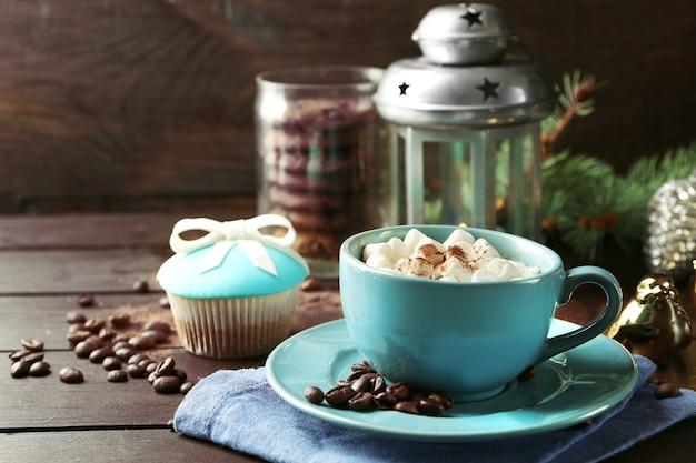 Кружка горячего шоколада с зефиром, ветка ели на деревянной поверхности