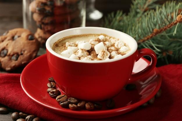 マシュマロとホットチョコレートのマグカップ、木製のテーブルの上のモミの木の枝