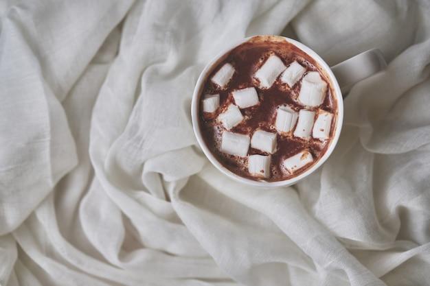 Кружка горячего шоколада с зефиром на светлом текстильном фоне. белая кружка горячего напитка крупным планом. вид сверху.