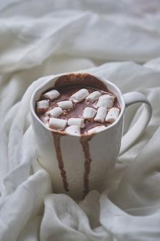 Кружка горячего шоколада с зефиром на светлом текстильном фоне. белая кружка горячего напитка крупным планом.