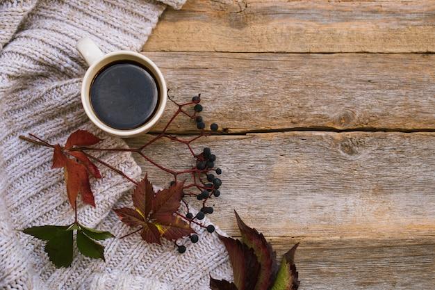 ニットのスカーフ、セーターと木製のテーブルの上に秋の設定でホットコーヒーのマグカップ。快適さ、暖かさ、居心地の良い