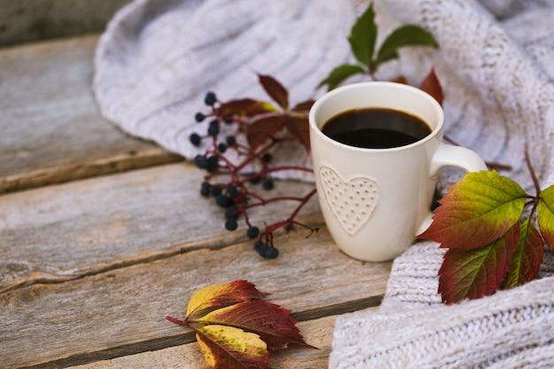 ニットのスカーフ、セーターと木製のテーブルに秋の設定でホットコーヒーのマグカップ