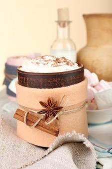 木製のテーブルにフェルトで飾られた温かい飲み物のマグカップ