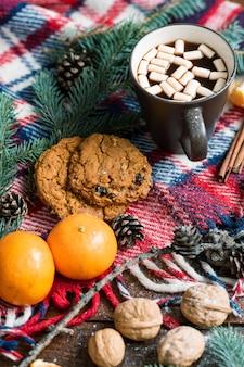 Кружка горячего чая или кофе с зефиром, грецкими орехами, мандаринами и печеньем на теплом шарфе