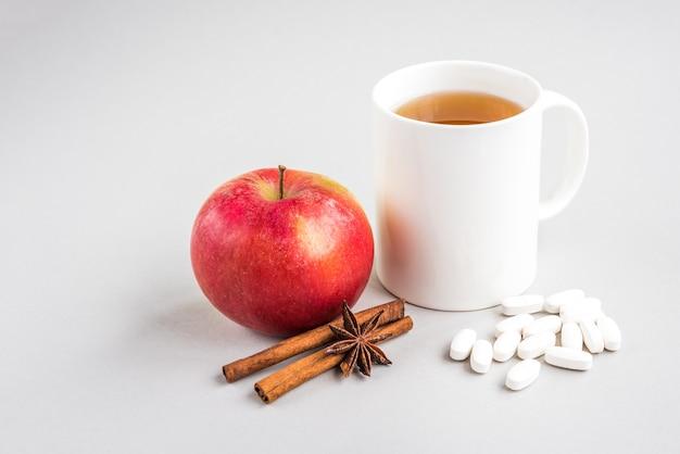 Кружка горячего чая с яблоком и корицей и таблетками на серой стене. сезонный грипп. болезнь.
