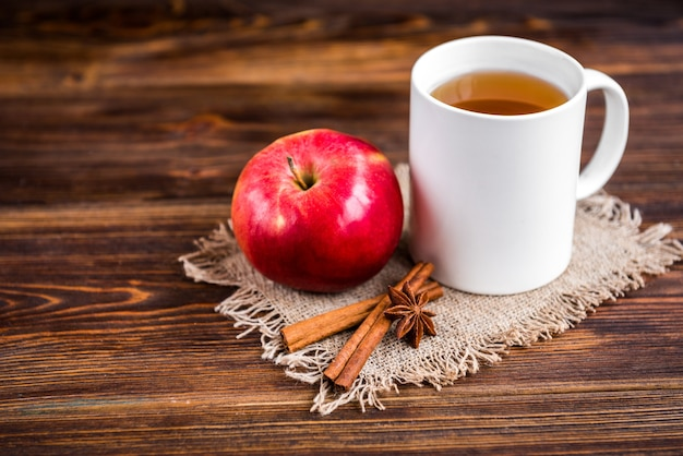Кружка горячего чая с яблоком и корицей на деревянной поверхности. сезонный грипп. болезнь.