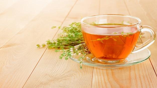 Кружка горячего чая со свежим тимьяном на деревянном столе