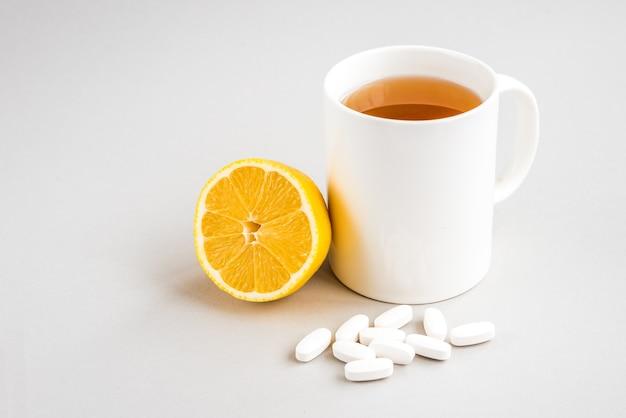 Кружка горячего чая с лимоном и таблетками на деревянной поверхности. катаральное заболевание. сезон гриппа.