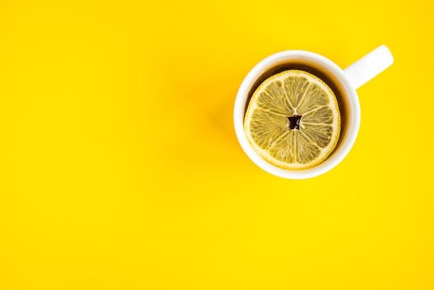 Кружка горячего чая с лимоном на желтом фоне. катаральное заболевание. сезон гриппа.