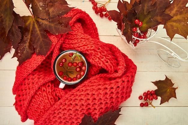Кружка горячего чая из калины с красным теплым вязанным шарфом