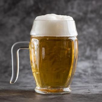 灰色の背景に軽いビールのジョッキ