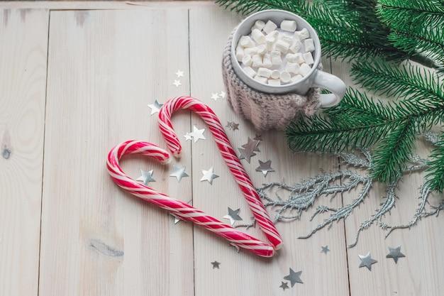 Кружка зефира и леденцов в окружении рождественских украшений на деревянном столе