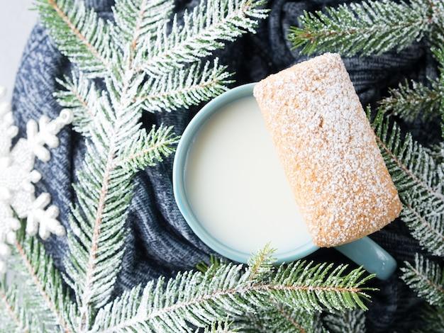 ミルクのマグカップと冬のクリスマス休暇に柔らかいウールのカーディガンのクッキー。