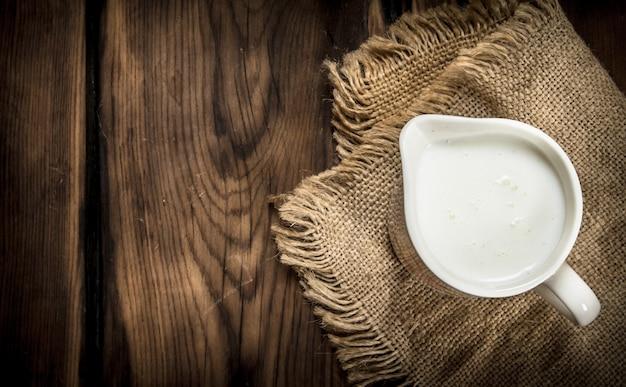 ミルクのマグカップ。木製のテーブルの上。