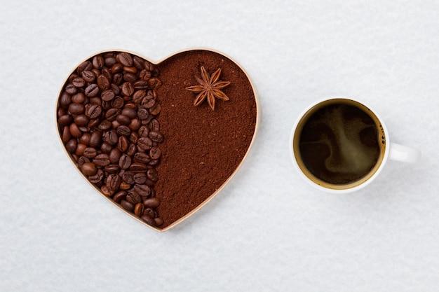 Кружка крепкого кофе и декоративное сердце. кофейные зерна и растворимый кофе в форме сердца, изолированные на белой поверхности