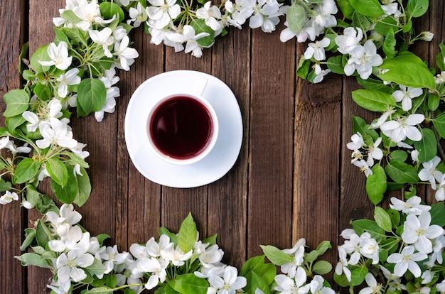 木製の背景にリンゴの花の中でお茶のマグカップ