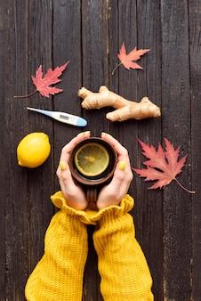 女性の手にお茶のマグカップ。レモン、生姜、温度計