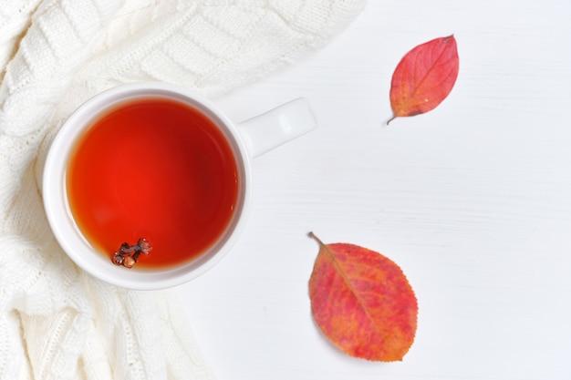 秋の乾燥葉とセーターと木製の背景のお茶のマグ。